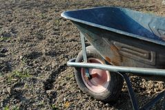 Old wheel barrow over soil Stock Photos