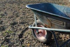 Old wheel barrow over soil. In the garden Stock Photos