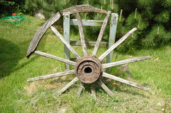 Old wheel. Old devastated wooden wagon wheel standing in garden royalty free stock photography