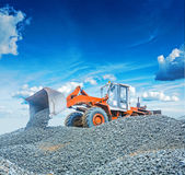 Old wheel loader excavator working with  gravel Stock Image
