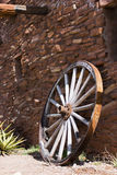 Old wheel near a stone wall Royalty Free Stock Photo
