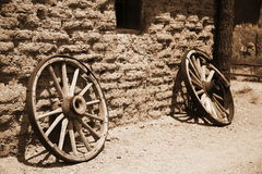 Old wheel from vintage cart beside wall Royalty Free Stock Images