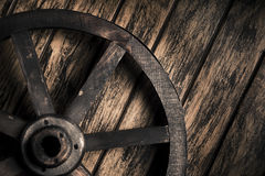 Old wheel on a wooden background Stock Image