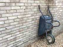 Old wheelbarrow being stored. Wheelbarrow being stored against the side of a house - copy space provided Stock Photo