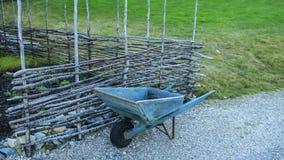Old wheelbarrow and fence Stock Photo