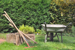 Old wheelbarrow and gardening tools Stock Images