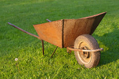 Old wheelbarrow in green grass Stock Photo