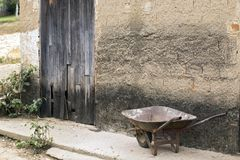 Old wheelbarrow leaning against apparent plaster wall Royalty Free Stock Images