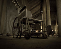 An old wheelchair in old room. old wheelchair was forsaken. this is lonely and scary concept. Royalty Free Stock Photography