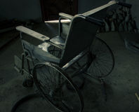An old wheelchair in old room. old wheelchair was forsaken. this is lonely and scary concept. Royalty Free Stock Images