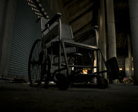 An old wheelchair in old room. old wheelchair was forsaken. this is lonely and scary concept. Royalty Free Stock Image