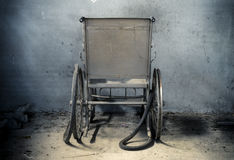 An old wheelchair in old room. old wheelchair was forsaken. this is lonely and scary concept. Stock Photo
