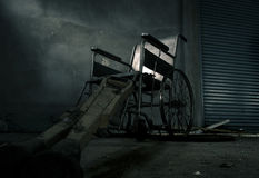 An old wheelchair and old wooden crutches in old room. old wheelchair was forsaken. this is lonely and scary concept. Royalty Free Stock Photos
