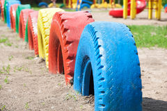 Old wheels of different colors on the playground in the park. Stock Image