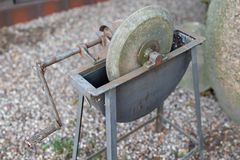 An old whetstone for sharpening knives. Grinding wheel on an old. Tripod. Season of the autumn royalty free stock image