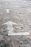 Old white arrow marking on the road Royalty Free Stock Photos