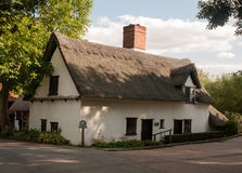 An old white barn cottage with thatched roof in summer light royalty free stock images