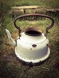 Old white battered kettle on meadow Royalty Free Stock Photography