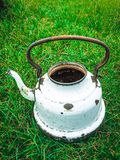 Old white battered kettle on meadow Stock Photo