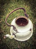 Old white battered kettle on meadow Stock Photos