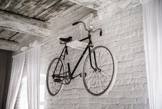 Old white bicycle whist on a white stone wall. Details of the old bicycle stock photos