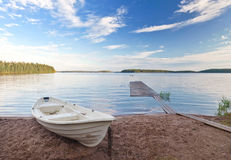 Old white boat on the coast of Saimaa lake, Finla. Landscape with old white boat on the coast of Saimaa lake, Finland royalty free stock images