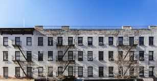 Old white brick apartment building with windows and fire escapes in New York City royalty free stock photo