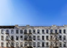 Free Old White Brick Apartment Building With Windows And Fire Escapes And An Empty Blue Sky Background Overhead In New York City Stock Photo - 141610600