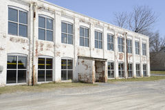 Old white brick factory building. Exterior of an old brick building which has been painted white. The structure could be a factory, warehouse,office royalty free stock photos