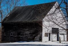 Old white and brown New England barn in a snowy field. Deep blue skies, wooden sides, warm March day royalty free stock photos