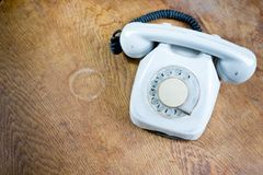 Old white cable telephone on old table surface. Communication technology from 80s royalty free illustration