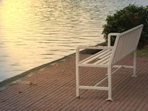 The old white chair standing by the river at sunrise royalty free stock images