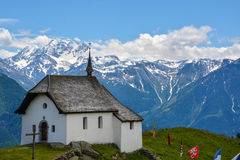 An old white chapel with the mountains in the background stock image