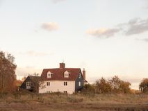 Old white country farm house cottage in field stock image