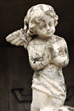 An Old White Crumbling Cherub Angel Statue Stock Image