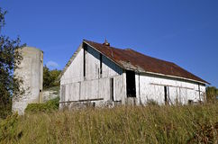 Old white deteriorating barn and silo Stock Photo