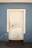 Old white door. On a blue wall Stock Photography