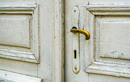 Old white door with golden doorknob. Closeup view Royalty Free Stock Images