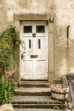An old white door with a wooden bucket stock photo