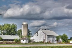 Old white farm buildings and an old silo. Old white farm buildings against a cloudy sky Stock Photography
