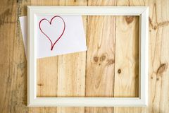 Old white frame Vintage frame with drawings love and heart. On paper wooden background royalty free stock photos