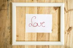 Old white frame Vintage frame with drawings love and heart on. Paper wooden background royalty free stock photos
