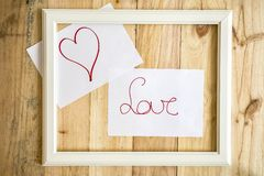 Old white frame Vintage frame with drawings love and heart. On paper wooden background stock image