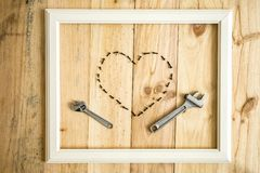 Old white frame Vintage frame with varied tools with heart shape. On wooden background stock image