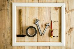 Old white frame Vintage with varied tools forming the word love. On wooden background royalty free stock photo