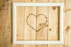 Old white frame Vintage frame with varied tools with heart shape. On wooden background royalty free stock image