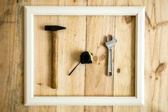 Old white frame Vintage frame with varied tools. On wooden background royalty free stock image