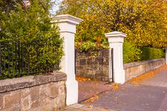 Old, white gate at the old house in Autumn. Beautiful, golden autumn scenery with trees and golden leaves in the sunshine in Scotland stock photo