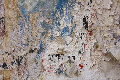 Old white gray damaged concrete wall with cracks and peeling blue red black paint. rough surface texture. A old white gray damaged concrete wall with cracks and stock photo