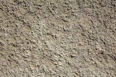 Old white gray yellow shabby wall with deep uneven relief and shadows. rough surface texture. A old white gray yellow shabby wall with deep uneven relief and royalty free stock photography